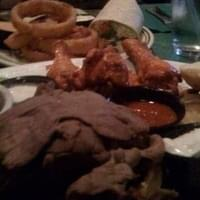 Foreground: Buffalo Platter close up with top bun…